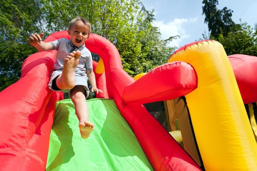Kind auf Hüpfburg Rutsche bei einem Riesen Spielefest