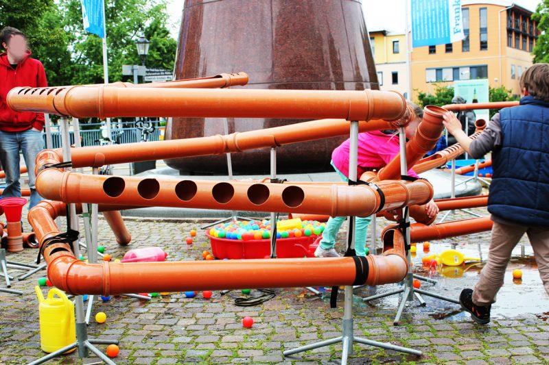 Spielende Kinder an einer Wasserbaustelle