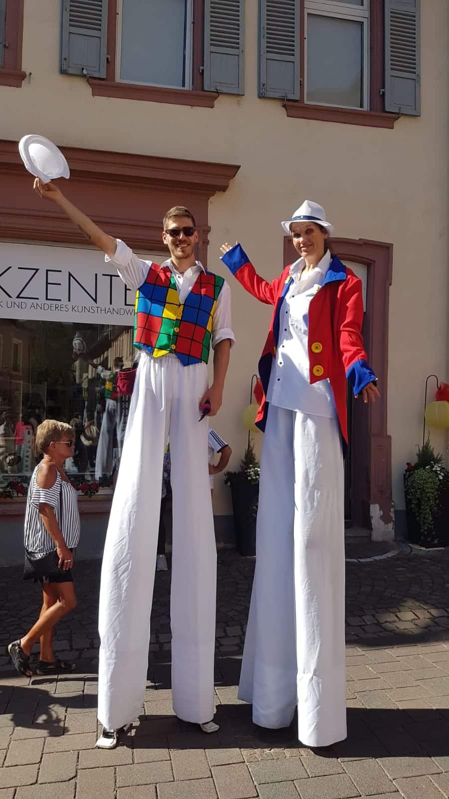 Stelzenläufer winken auf einem Strassenfest den Passanten zu